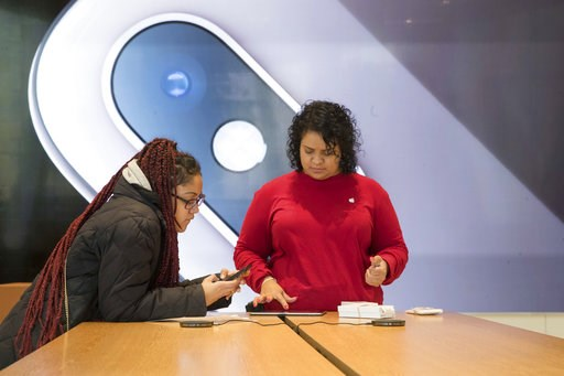 (AP Photo/Mary Altaffer). An image of an iPhone is on display in the background as a customer, left, is helped at the Apple store in the Brooklyn borough of New York, Thursday, Jan. 3, 2019. Apple's shock warning that its Chinese sales are weakening ra...