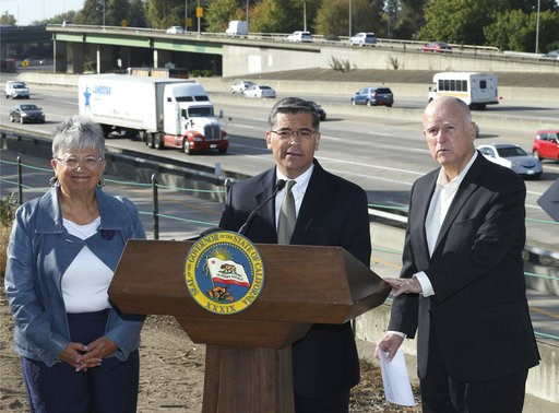 (AP Photo/Rich Pedroncelli, File). FILE - In this Oct. 26, 2018 file photo, California Attorney General Xavier Becerra, center, discusses a Trump administration plan to freeze vehicle emissions standards during a news conference in Sacramento, Calif. B...