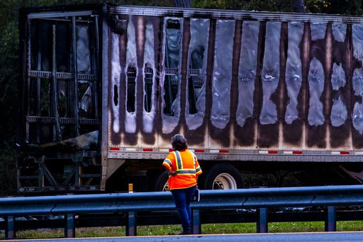 (Lauren Bacho/The Gainesville Sun via AP). CORRECTS SOURCE TO THE GAINESVILLE SUN A worker looks at a charred semi-truck after a wreck with multiple fatalities on Interstate 75, south of Alachua, near Gainesville, Fa., Thursday, Jan. 3, 2019. Two big r...