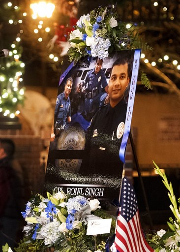 (Andy Alfaro/The Modesto Bee via AP, File). FILE - This Friday, Dec. 28, 2018 file photo shows a collection of pictures of police Cpl. Ronil Singh during a candlelight vigil in Newman, Calif. The Northern California police officer was gunned down durin...