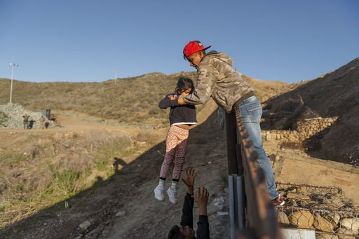 (AP Photo/Daniel Ochoa de Olza). A migrant from Honduras pass a child to her father after he jumped the border fence to get into the U.S. side to San Diego, Calif., from Tijuana, Mexico, Thursday, Jan. 3, 2019. Discouraged by the long wait to apply for...