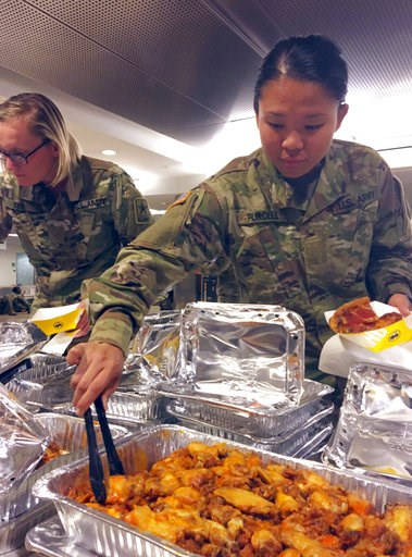 (Josh Ryan/Oklahoma City Airport via AP). In this Thursday, Jan. 3, 2018 photo, provided by the Oklahoma City Airport, stranded soldiers at Will Rogers World Airport in Oklahoma City, are treated to donated food during a winter storm. Hundreds of soldi...