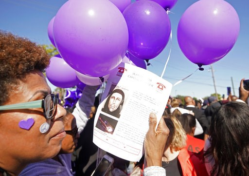 (Melissa Phillip/Houston Chronicle via AP). Donna Thomas holds a flyer about the shooting suspect as she attends a community rally for seven-year-old Jazmine Barnes on Saturday, Jan. 5, 2019 in Houston.   Barnes was killed  when a driver shot into the ...