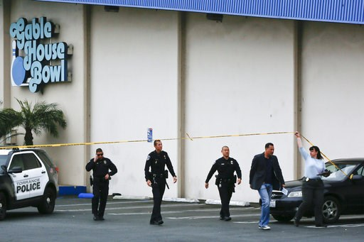 (AP Photo/Damian Dovarganes). Torrance Police Department investigators walk towards waiting family members, as officers confirm fatalities in a shooting incident at the Gable House Bowl in Torrance, Calif., Saturday, Jan. 5, 2019. A brawl between two l...