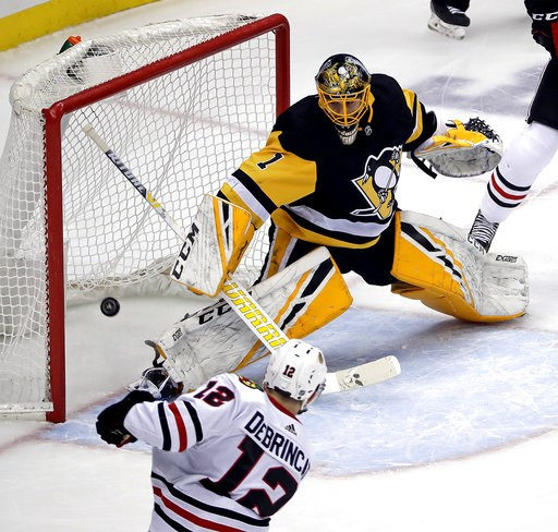 (AP Photo/Gene J. Puskar). Chicago Blackhawks' Alex DeBrincat (12) puts the puck past Pittsburgh Penguins goaltender Casey DeSmith (1) for a power play goal in the first period of an NHL hockey game in Pittsburgh, Sunday, Jan. 6, 2019.