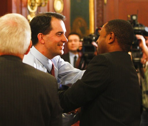 (AP Photo/Andy Manis File). FILE - In this June 6, 2016 file photo, Wisconsin Gov. Scott Walker, center, shakes hands with Wisconsin Department of Workforce Development Secretary Reggie Newson at a cabinet meeting at the state Capitol in Madison, Wis.,...