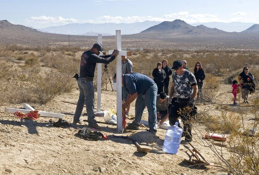 (James Quigg/The Victor Valley Daily Press via AP, File). FILE - In this Nov. 20, 2013, file photo, people place crosses near the graves where the McStay family was found in Victorville, Calif.  Opening statements are expected on Monday, Jan. 7, 2019, ...