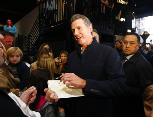 (AP Photo/Rich Pedroncelli). Governor-elect, Lt. Gov. Gavin Newsom, center, autographs a copy of his book, Citizenville for a well-wisher while attending a pre-inaugural Family Event held at the California Railroad Museum, Sunday, Jan. 6, 2019, in Sacr...