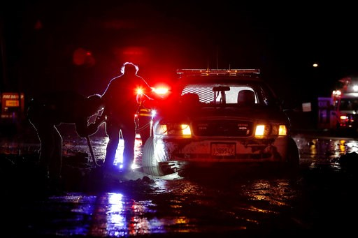 (Luis Sinco/Los Angeles Times via AP). In this Saturday, Jan 5, 2019, photo sheriff's deputies work to free their patrol cruiser from mud covering a stretch of Pacific Coast Highway in Malibu, Calif. A winter storm unleashed mudslides in Southern Calif...