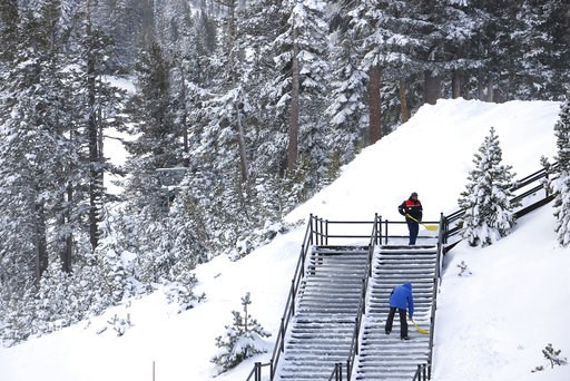 (Jason Bean/The Reno Gazette-Journal via AP, File). FILE - In this Nov. 29, 2018, file photo, workers shovel snow off a staircase at Mt. Rose Ski Tahoe near Reno, Nev. Avalanche warnings have been posted in parts of California, Nevada and Utah after a ...