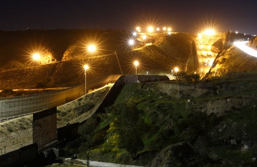 """(AP Photo/Gregory Bull). Floodlights from the U.S, illuminate multiple border walls Monday, Jan. 7, 2019, seen from Tijuana, Mexico. With no breakthrough in sight, President Donald Trump will argue his case to the nation Tuesday night that a """"crisis"""" a..."""