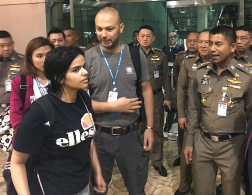 (Immigration police via AP). In this photo released by the Immigration Bureau, Saudi woman Rahaf Mohammed Alqunun, foreground walks by Chief of Immigration Police Maj. Gen. Surachate Hakparn, right, before leaving the Suvarnabhumi Airport in Bangkok Mo...