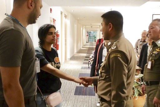 (Immigration police via AP). In this photo released by the Immigration Police,  Saudi woman Rahaf Mohammed Alqunun, second left, shakes hand with Chief of Immigration Police Maj. Gen. Surachate Hakparn before leaving the Suvarnabhumi Airport in Bangkok...
