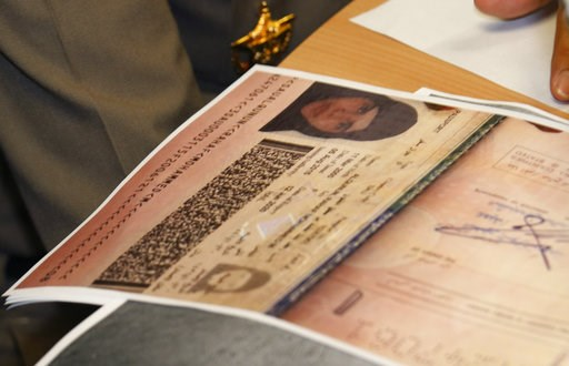 (AP Photo/Sakchai Lalit). A passport copy of Rahaf Mohammed Alqunun sits on the desk as Chief of Immigration Police Maj. Gen. Surachate Hakparn talks to media about her status during a press conference at the Suvarnabhumi Airport in Bangkok Monday, Jan...