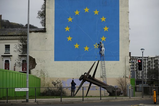 (AP Photo/Matt Dunham). A man takes a photograph of a mural by street artist Banksy, depicting a star being chiselled from the European flag in Dover, south-east England, Monday, Jan. 7, 2019. Britain is testing how its motorway and ferry system would ...