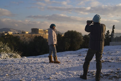(AP Photo/Petros Giannakouris). A tourist poses for a picture at Filopappos hill as at the background is seen the ancient Acropolis hill with the 500BC Parthenon temple, after snowfall in Athens, on Tuesday, Jan. 8, 2019.
