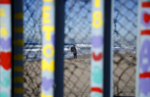 (AP Photo/Gregory Bull). Two people embrace on the U.S. side of the border, seen through the border wall Monday, Jan. 7, 2019, seen from along the beach in Tijuana, Mexico. U.S. Vice President Mike Pence said Monday the White House is looking into the ...