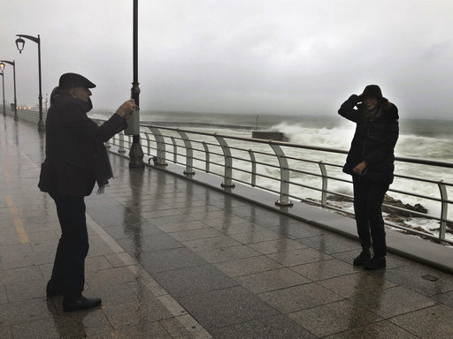 (AP Photo/Hussein Malla). Walid Jumblatt, left, the political leader of Lebanon's minority Druse sect, takes pictures of his wife Nura, as waves break, on the Mediterranean waterfront, in Beirut, Lebanon, Tuesday, Jan. 8, 2019. A strong storm in Lebano...