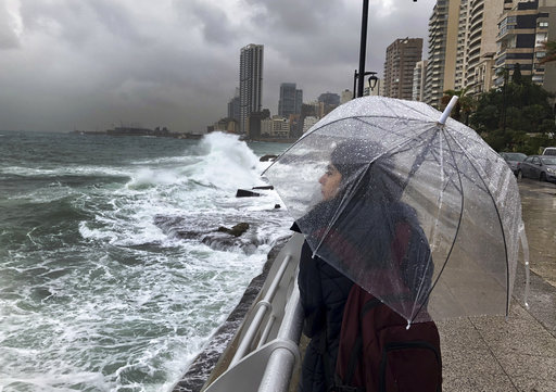 (AP Photo/Hussein Malla). A Lebanese girl shelters for the rain, as she watches waves crash into the seawall on the Mediterranean Sea, in Beirut, Lebanon, Tuesday, Jan. 8, 2019. A strong storm in Lebanon brought cold temperatures and snow to Lebanon's ...