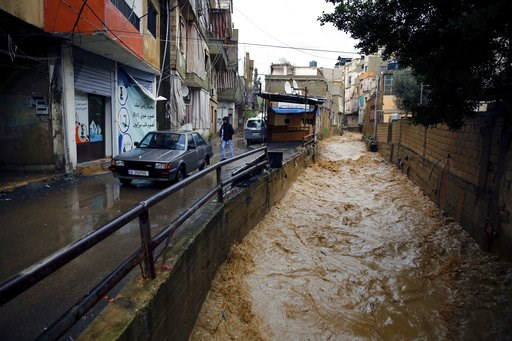 (AP Photo/Bilal Hussein). People walk next to a canal that flows from rainwater in Beirut, Lebanon, Tuesday, Jan. 8, 2019. A strong storm and heavy rainfall turned streets in Lebanon into rivers of water and mud and paralyzed parts of the country. The ...