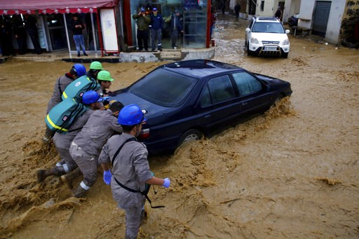 (AP Photo/Bilal Hussein). Civil Defense workers struggle to push a stranded car on a street in Beirut, Lebanon, Tuesday, Jan. 8, 2019. A strong storm and heavy rainfall turned streets in Lebanon into rivers of water and mud and paralyzed parts of the c...