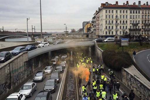 (AP Photo/Laurent Cipriani). Demonstrators wearing yellow vests walk on the highway in Lyon, central France, Saturday, Jan. 5, 2019. Protesters were looking to breathe new life into the yellow vest movement as numbers of participants fell since the fir...