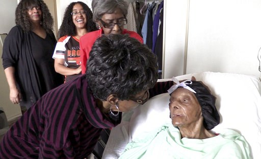 (David Petkiewicz/The Plain Dealer via AP). FILE - In this Sept. 22, 2018 file photo, Lessie Brown, right, is visited by her daughters, Verline Wilson, foreground, and Vivian Hatcher, third from left, and other family and friends at her home in Clevela...