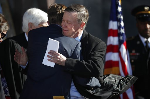 (AP Photo/David Zalubowski, Pool). Teddy Hickenlooper, left, hugs his father, John Hickenlooper, after his final speech as Colorado's governor at the inauguration ceremony for the new governor, Jared Polis, Tuesday, Jan. 8, 2019, in Denver.