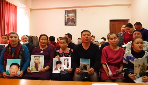 (AP Photo/Dake Kang). In this Dec. 7, 2018, image made from video, relatives of people missing in China's far western region of Xinjiang hold up photos at an office of a Chinese Kazakh advocacy organization in Almaty, Kazakhstan. The Kazakhstan Foreign...