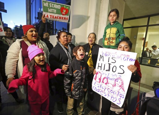 (AP Photo/Reed Saxon). Adults and children stand nearby as United Teachers Los Angeles union president Alex Caputo-Pearl, not shown, talks to reporters outside Los Angeles Unified School District headquarters, following a day of negotiations with the L...