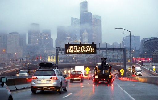 (AP Photo/Elaine Thompson). In this photo taken Thursday, Jan. 3, 2019, rush hour northbound Highway 99 traffic backs-up while heading toward the Alaskan Way Viaduct just ahead as a sign overhead advises of an upcoming closure of the roadway in Seattle...