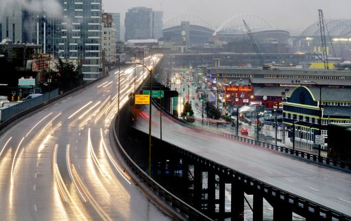 (AP Photo/Elaine Thompson). In this long-exposure photo taken Thursday, Jan. 3, 2019, headlights and taillights of Alaskan Way Viaduct traffic lines the highway ahead of an upcoming closure of the roadway, as the city's sports stadiums are seen in the ...