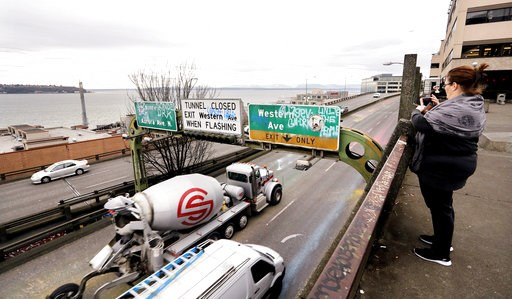 (AP Photo/Elaine Thompson). In this photo taken Wednesday, Jan. 2, 2019, a woman takes a photo toward Elliott Bay as Alaskan Way Viaduct traffic rolls past her below ahead of an upcoming closure of the roadway, in Seattle. The double-decker highway alo...