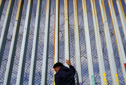 (AP Photo/Gregory Bull). A man holds on to the border wall along the beach, Tuesday, Jan. 8, 2019, in Tijuana, Mexico. Ready to make his case on prime-time TV, President Donald Trump is stressing humanitarian as well as security concerns at the U.S.-Me...