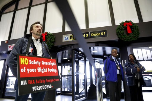 (AP Photo/Julio Cortez). Federal Aviation Administration employee Michael Jessie, who is currently working without pay as an aviation safety inspector for New York international field office overseeing foreign air carriers, holds a sign while attending...