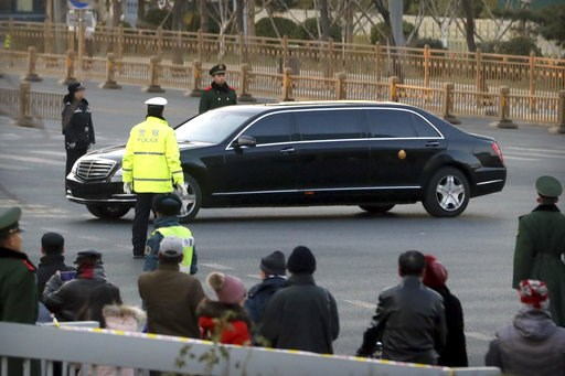 (AP Photo/Mark Schiefelbein). Spectators watch as security officials stand guard while a Mercedes limousine in a motorcade believed to be carrying North Korean leader Kim Jong Un passes along a street in Beijing, Wednesday, Jan. 9, 2019. North Korean s...