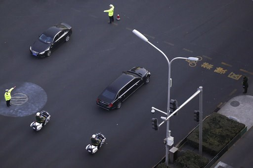 (AP Photo/Andy Wong). Traffic policemen direct traffic as a Mercedes limousine with a golden emblem, similar to one North Korean leader Kim Jong Un has used previously, is escorted by motorcades traveling past Chang'an Avenue in Beijing, Wednesday, Jan...