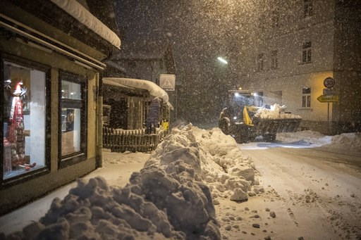 (Lino Mirgeler/dpa via AP). A digger removes shnow in the city center of Miesbach, Germany, Wednesday, Jan. 9, 2019. Due to heavy snow fall the Miesbach county announced a disater alert.