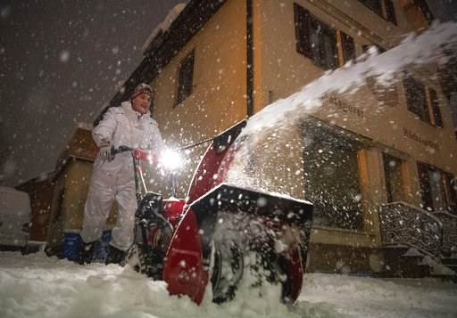 (Lino Mirgeler/dpa via AP). A man removes shnow in the city center of Miesbach, Germany, Wednesday, Jan. 9, 2019. Due to heavy snow fall the Miesbach county announced a disater alert.