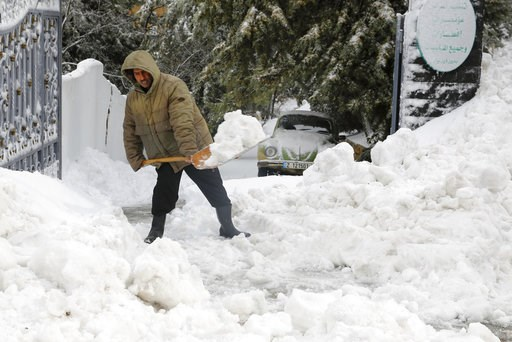 (AP Photo/Bilal Hussein). Ahmed al-Hamdan shovels snow from the sidewalk around the hotel where he works,  in the village of Sawfar, Mount Lebanon, Wednesday, Jan. 9, 2019. A storm of snow and heavy rain that has battered Lebanon for five days has kill...