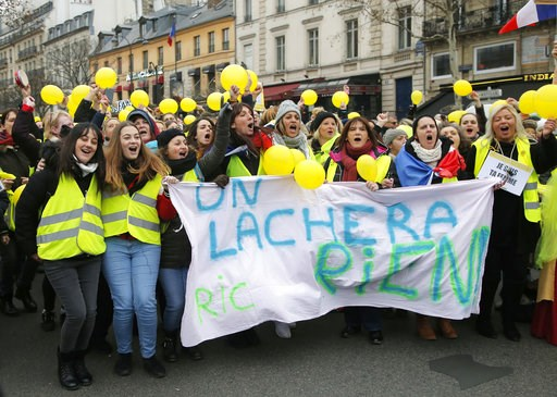 (AP Photo//Michel Euler). Women wearing yellow vests and holding yellow balloons march during a protest in Paris, Sunday, Jan. 6, 2019. Several hundred women wearing yellow vests march during a rally in Paris to give a different image to the movement.