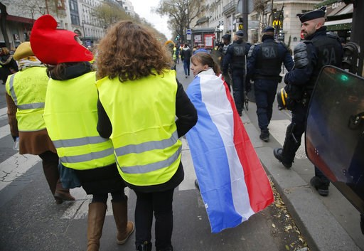 (AP Photo//Michel Euler). Women wearing yellow vests and a French national flag are escorted by riot police officers during a protest in Paris, Sunday, Jan. 6, 2019. Several hundred women wearing yellow vests march during a rally in Paris to give a dif...