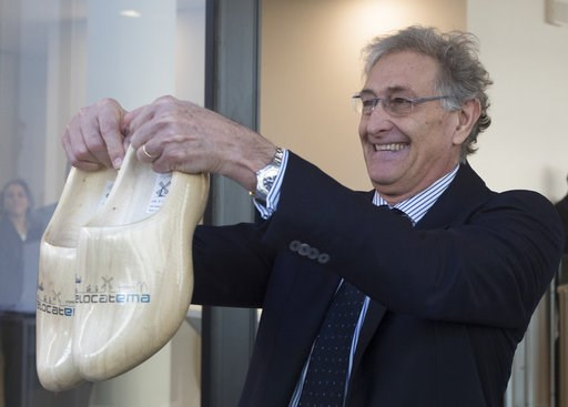 (AP Photo/Peter Dejong). In a sign of the looming Brexit, Italy's Guido Rasi, director of the European Medicines Agency holds a pair of wooden shoes he was presented by Dutch Health Minster Bruno Bruins during the official opening of the agency's tempo...