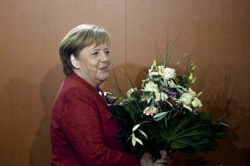 (AP Photo/Markus Schreiber). German Chancellor Angela Merkel arrives with flowers for the weekly cabinet meeting of the German government at the chancellery in Berlin, Germany, Wednesday, Jan. 9, 2019. The flowers are a birthday present for the Governm...