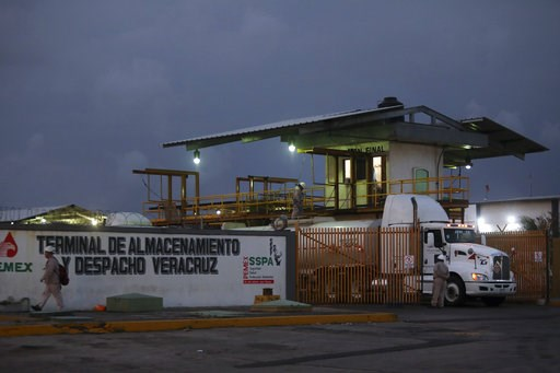 (AP Photo/Felix Marquez). Tanker trucks stand at the exit of a Petroleos Mexicanos, or Pemex, fuel depot and distribution center in the port city of Veracruz, Mexico, Wednesday, Jan. 9, 2019, as tankers exit under police escort to carry fuel to parts o...
