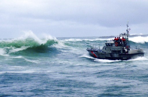 (U.S. Coast Guard via AP). In this Tuesday, Jan. 8, 2019 photo, provided by the U.S. Coast Guard, a U.S. Coast Guard boat crew responds to three fishermen in the water after the commercial fishing vessel Mary B II capsized while crossing Yaquina Bay Ba...