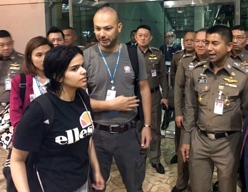 (Immigration police via AP, File). FILE - In this Jan. 7, 2019, file photo released by the Immigration Bureau, Saudi woman Rahaf Mohammed Alqunun, foreground, walks by Chief of Immigration Police Maj. Gen. Surachate Hakparn, right, before leaving the S...