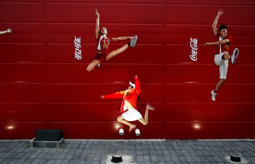 (AP Photo/Elizabeth Dalziel). FILE - In this Aug. 20, 2008 file photo, a young girl mimics the pose of a Chinese Olympic athletes depicted in Coca-Cola advertising, at the Olympic green in Beijing.   The International Life Science Institute, a group fu...