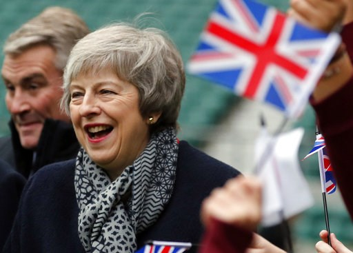 (AP Photo/Frank Augstein, Pool). Britain's Prime Minister Theresa May reacts ashildren play rugby, during a visit with Japanese Prime Minister Shinzo Abe to Twickenham Rugby Stadium, in London, Thursday, Jan. 10, 2019.