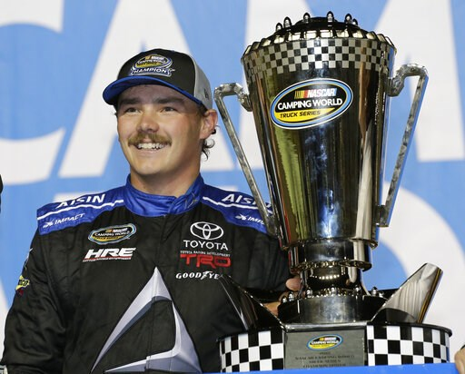 (AP Photo/Terry Renna, File). FILE - In this Nov. 16, 2018, file photo, Brett Moffitt stands with his trophy in Victory Lane after winning the NASCAR Trruck Series auto racing season championship, at Homestead-Miami Speedway in Homestead, Fla. A flurry...